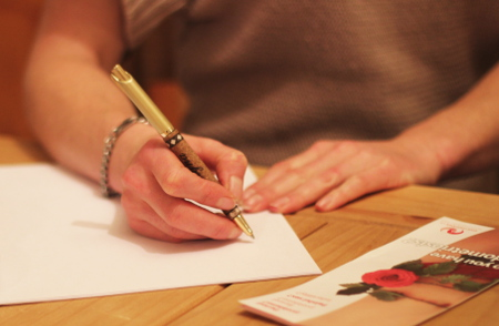 Image of a person writing a letter to share their story